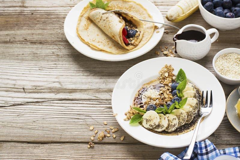 Sund frukosttrend Tunna havrepannkakor med bananen, blåbär, gojibär, sesam och chiafrö arkivfoton