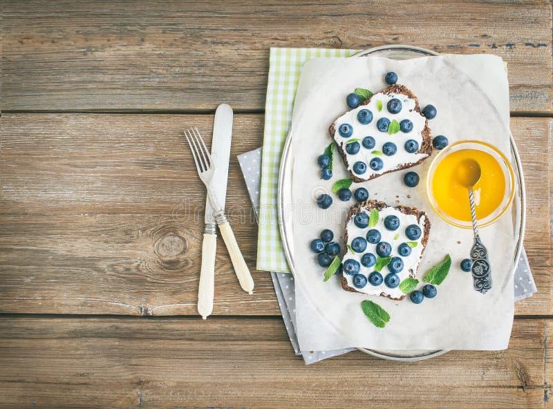 Sund frukostuppsättning med ricotta, nya blåbär, honung och royaltyfria foton