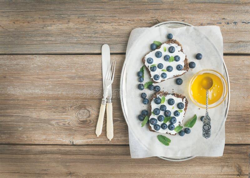 Sund frukostuppsättning med ricotta, nya blåbär, honung och arkivfoton