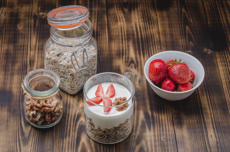 Sund frukostyoghurt, ny jordgubbe, hemlagad granola och valnöt i öppen exponeringsglaskrus på en trätabell arkivfoton