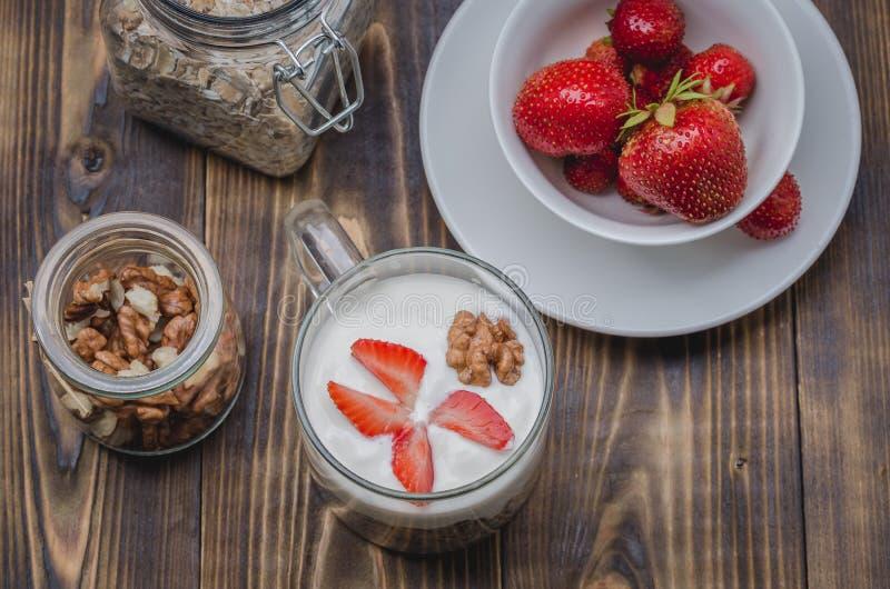 Sund frukostyoghurt, ny jordgubbe, hemlagad granola och valnöt i öppen exponeringsglaskrus på en trätabell Top besk?dar royaltyfria foton