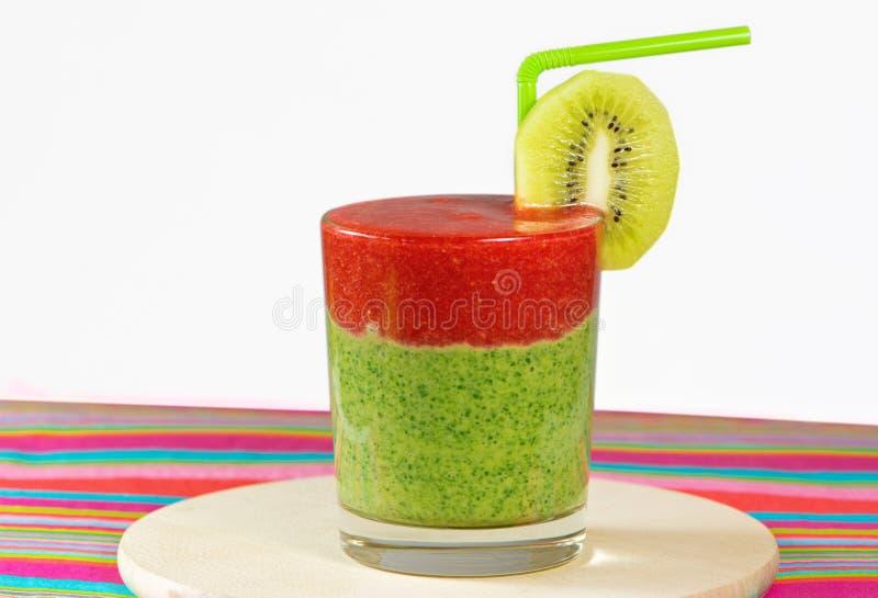 Sund gräsplan och röd smoothie med jordgubben, kiwi, äpplen, snurrande arkivfoto