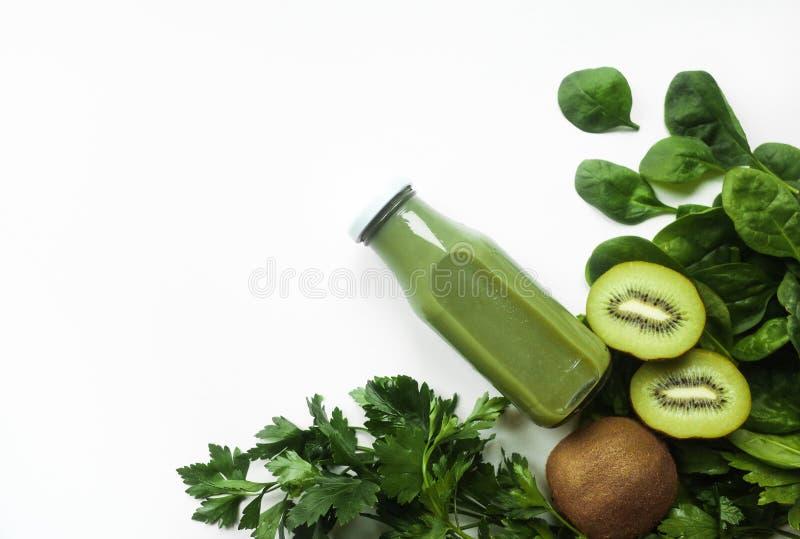 Sund grön smoothie eller fruktsaft och ingredienser på vitt - superfoods, detox, bantar, hälsa, vegetariskt matbegrepp kopiera av royaltyfria foton