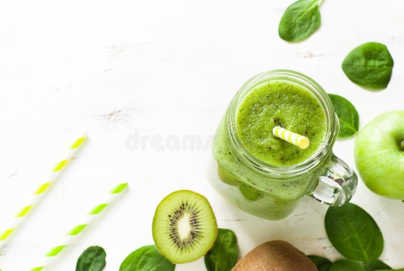 Sund grön smoothie i krus arkivbilder