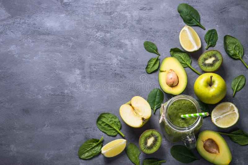 Sund grön smoothie i murarekrus och ingredienser arkivbilder