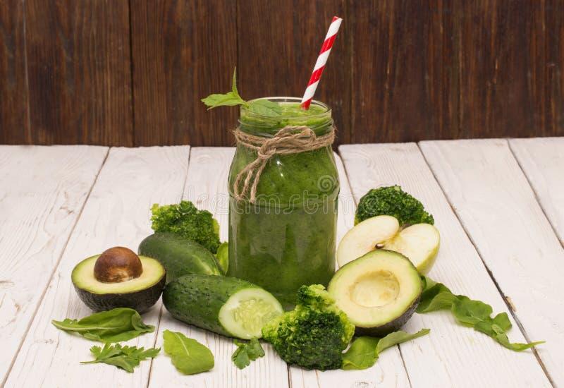 Sund grön smoothie med bananen, spenat, avokadot och gurkan i glasflaskor på ett lantligt royaltyfria bilder