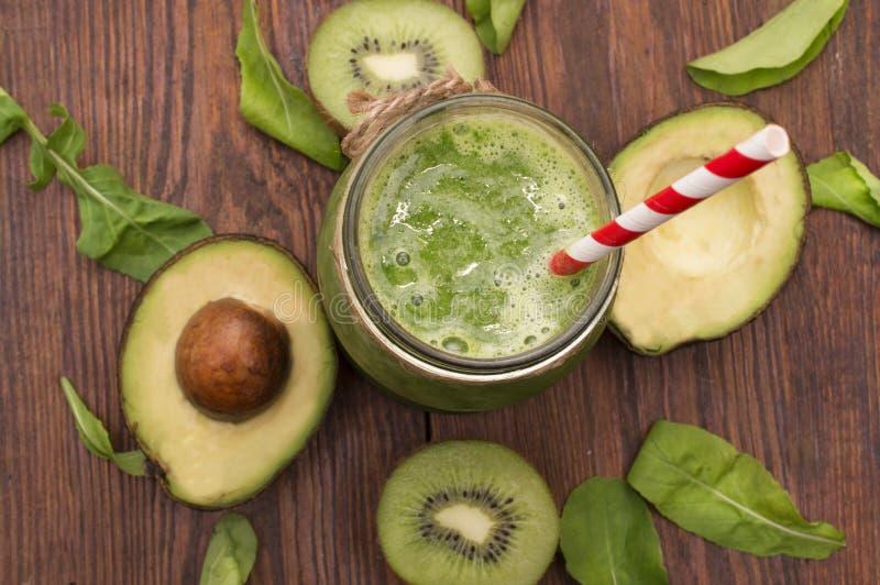 Sund grön smoothie med bananen, spenat, avokadot och kiwin i glasflaskor på ett lantligt arkivfoto