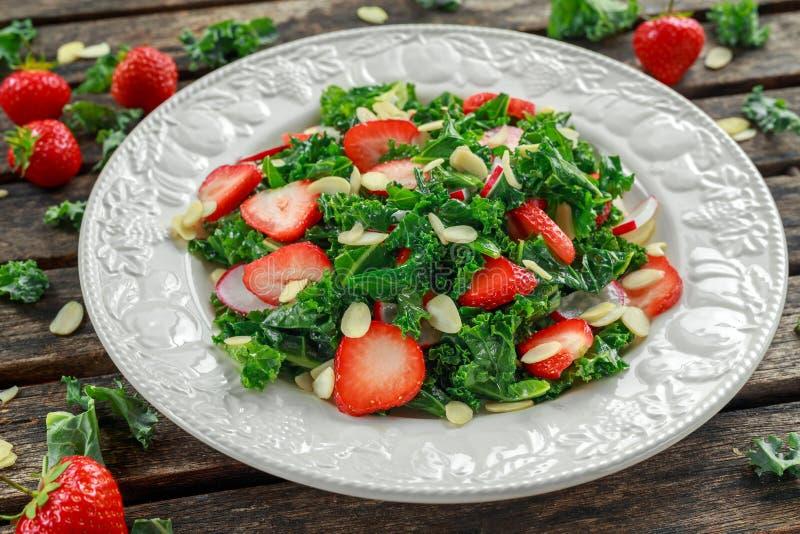 Sund grönkålsallad med jordgubbar och mandeln i en platta på trätabellen royaltyfri fotografi