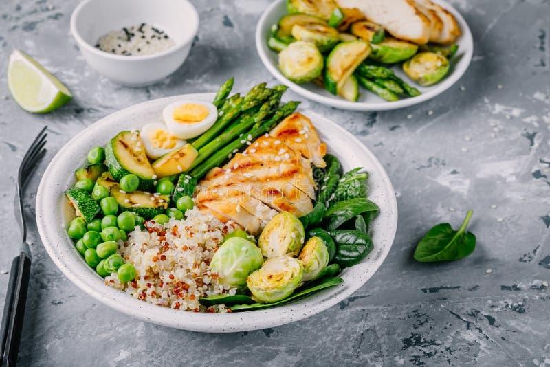 Sund grillad grönsakbuddha bunke med höna och quinoa, spenat, ägg, zucchini, sparris, Bryssel groddar och gröna ärtor arkivbilder