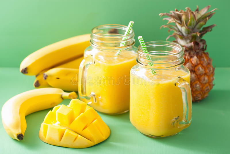 Sund gul smoothie med mangoananasbananen i murarekrus royaltyfria foton