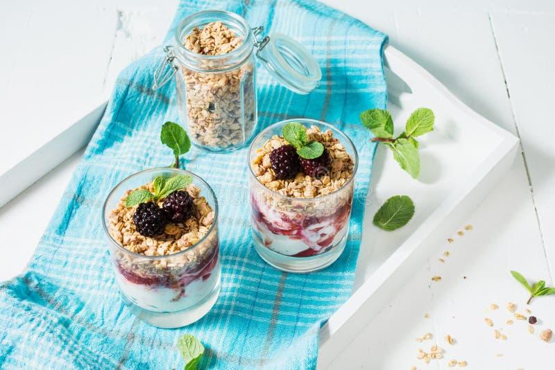 Sund i lager efterrätt med yoghurten, granola, driftstopp, björnbär i exponeringsglas på wood bakgrund arkivbild