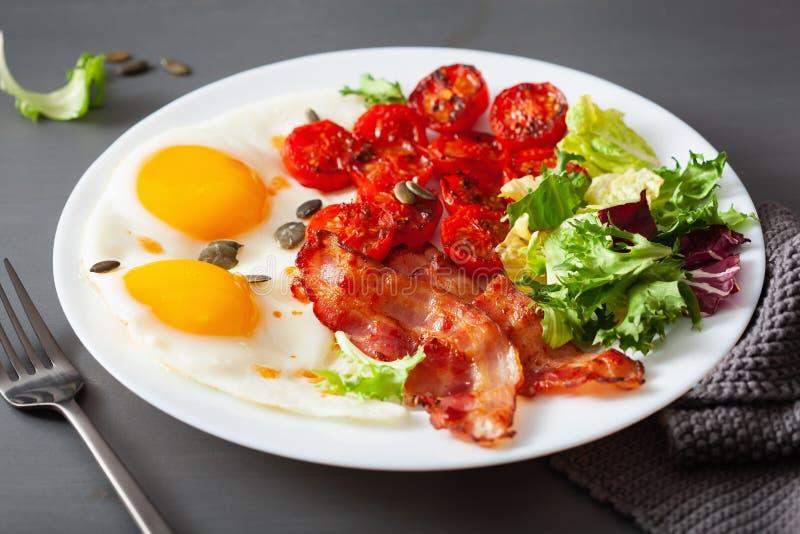 Sund keto bantar frukosten: ?gg, tomater, salladsidor och bacon royaltyfria bilder