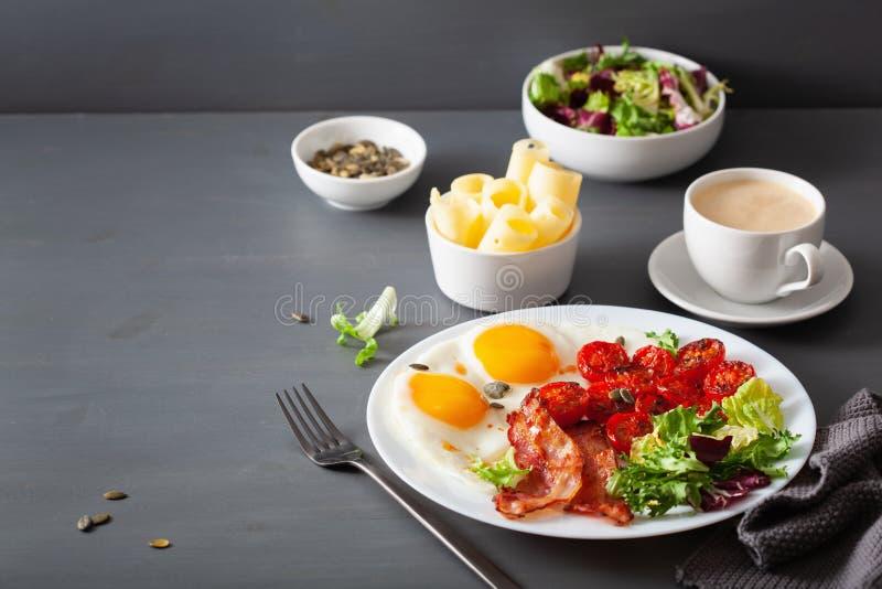 Sund keto bantar frukosten: ?gg, tomater, salladsidor och bacon royaltyfria foton