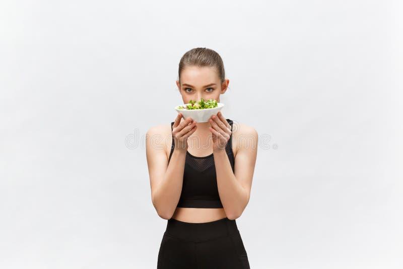 Sund konditionkvinna som äter sallad och att stå som isoleras på vit bakgrund arkivfoton