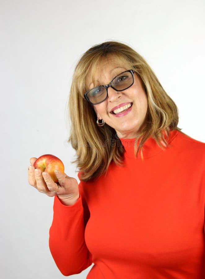 Sund kvinna i det röda förklädet som rymmer ett äpple fotografering för bildbyråer