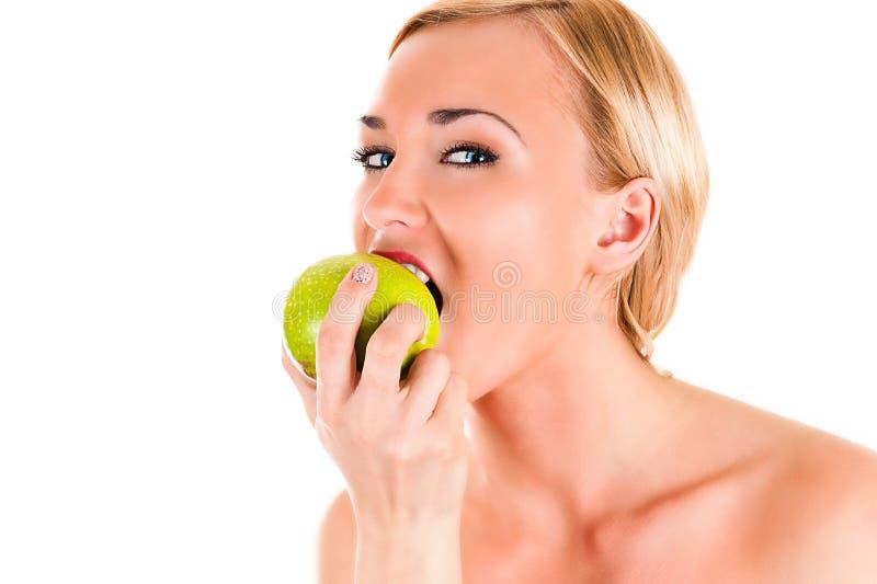 Sund kvinna som äter ett grönt äpple arkivbild