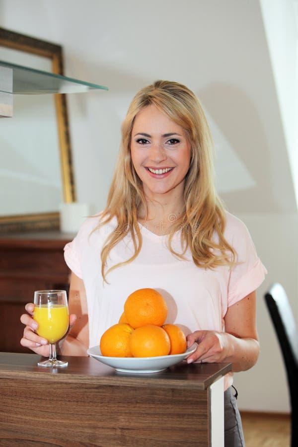 Sund kvinna som dricker ny orange fruktsaft royaltyfria bilder