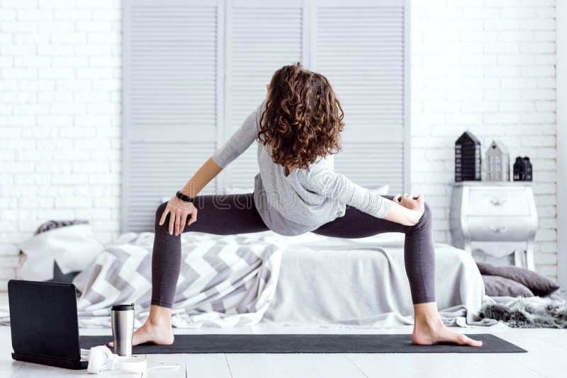 Sund kvinna som hemma g?r yogagenomk?rare arkivbilder