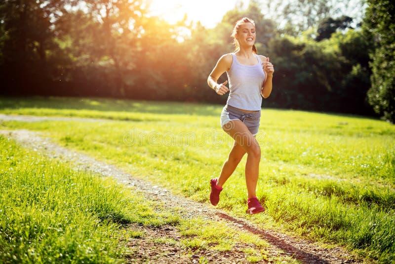 Sund kvinna som tidigt på morgonen joggar royaltyfri fotografi