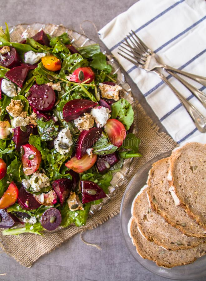 Sund läcker rödbetssallad och getost på variation av ny blandad sallad som garneras med pumpafrö och den balsamic vinrankan royaltyfri fotografi
