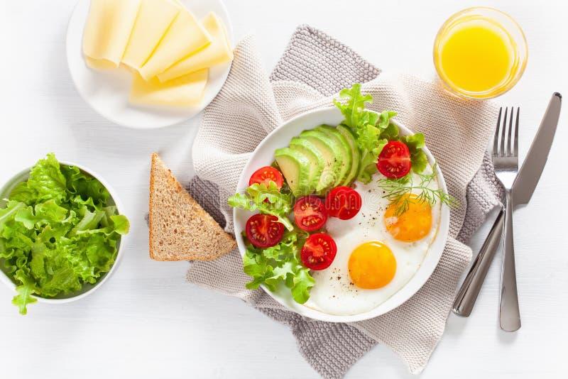 Sund lekmanna- frukostlägenhet stekte ägg, avokado, tomat, rostade bröd fotografering för bildbyråer