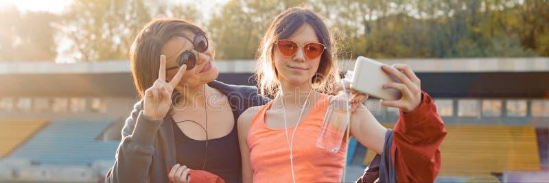 Sund livsstil, sund familj Le konditionmodern och den tonåriga dottern som poserar tillsammans på stadion, når att ha kört som är arkivbilder