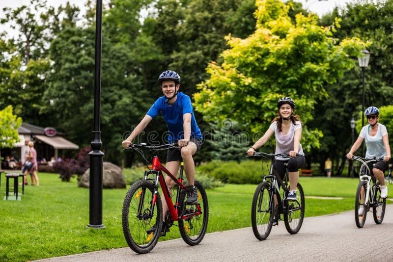 Sund livsstil - folket som rider cyklar i stad, parkerar arkivfoton