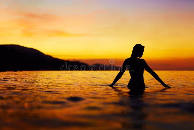 Sund livsstil, hälsa Kvinna som tycker om havssolnedgång Sommar vac fotografering för bildbyråer