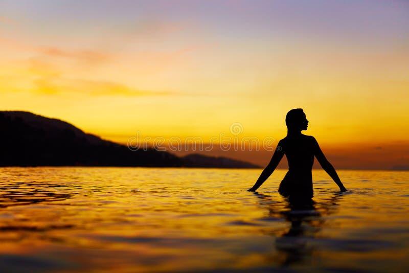 Sund livsstil, hälsa Kvinna som tycker om havssolnedgång Sommar vac royaltyfria bilder