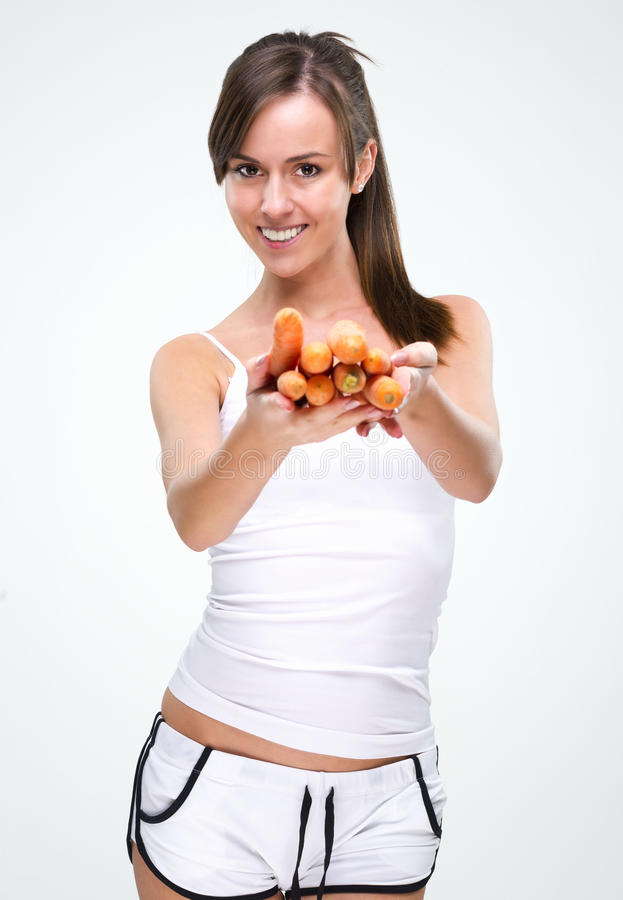 Sund livsstil! Hållande morot för härlig kvinna royaltyfri fotografi