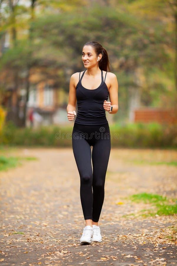 Sund livsstil Kvinna som joggar på skogslinga arkivbilder