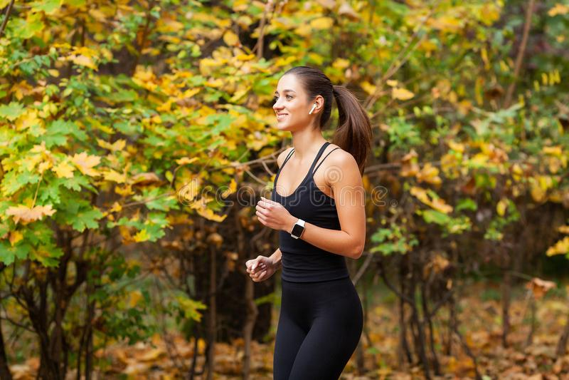Sund livsstil Kvinna som joggar på skogslinga arkivbild