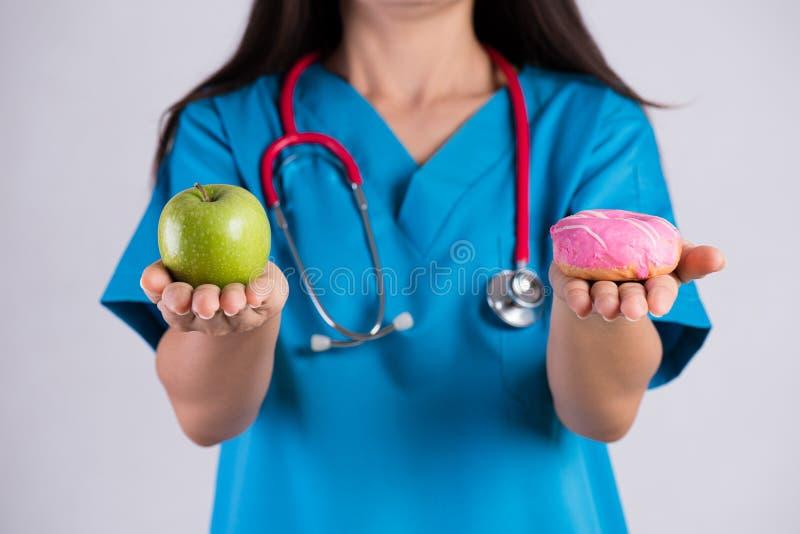 Sund livsstil, mat och sportbegrepp sunt sjukligt kontra Munk för innehav för doktorskvinnahand och grönt äpple arkivbild