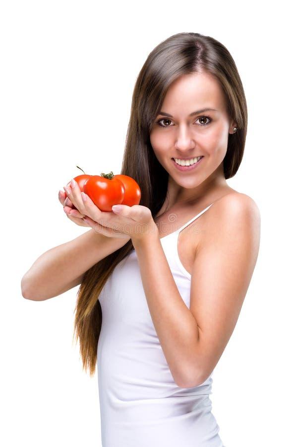 Sund livsstil! Nätt kvinna som rymmer en tomat royaltyfria foton