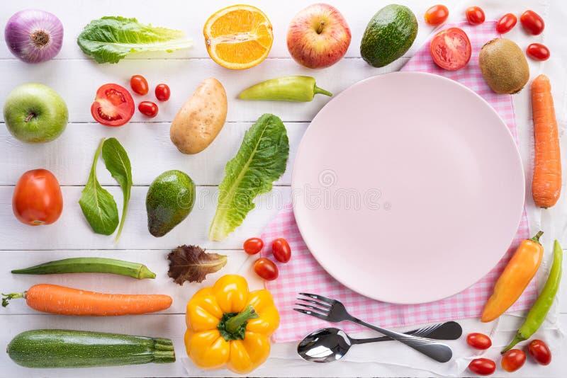 Sund livsstil och matbegrepp Bästa sikt av nya grönsaker, frukt, örter och kryddor med en tom rosa pastellfärgad platta på vit fotografering för bildbyråer