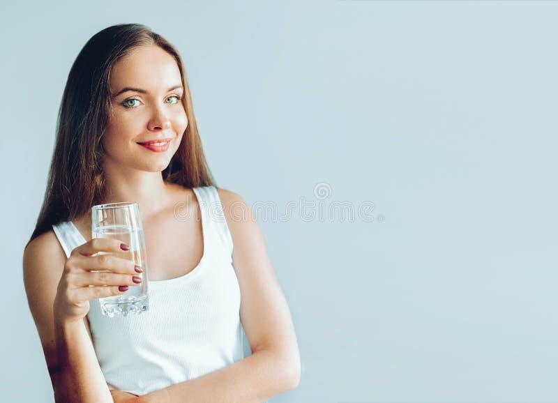 Sund livsstil Showexponeringsglas för ung kvinna av vatten dricker flickavatten Stående av den genomskinliga lyckliga le kvinnlig royaltyfri bild