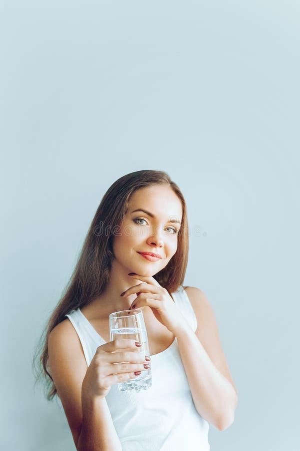 Sund livsstil Showexponeringsglas för ung kvinna av vatten dricker flickavatten Stående av den genomskinliga lyckliga le kvinnlig fotografering för bildbyråer