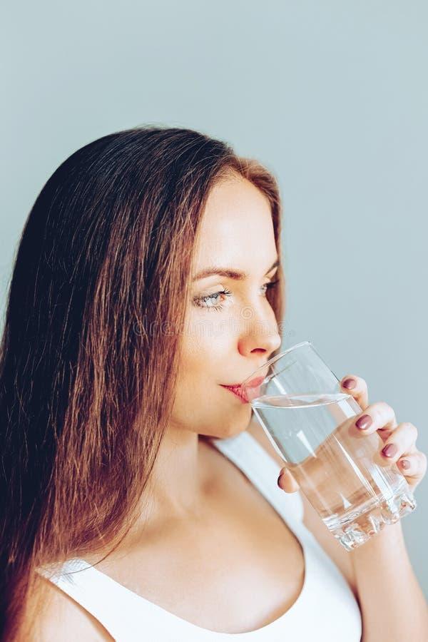 Sund livsstil Showexponeringsglas för ung kvinna av vatten dricker flickavatten Stående av den genomskinliga lyckliga le kvinnlig arkivfoton