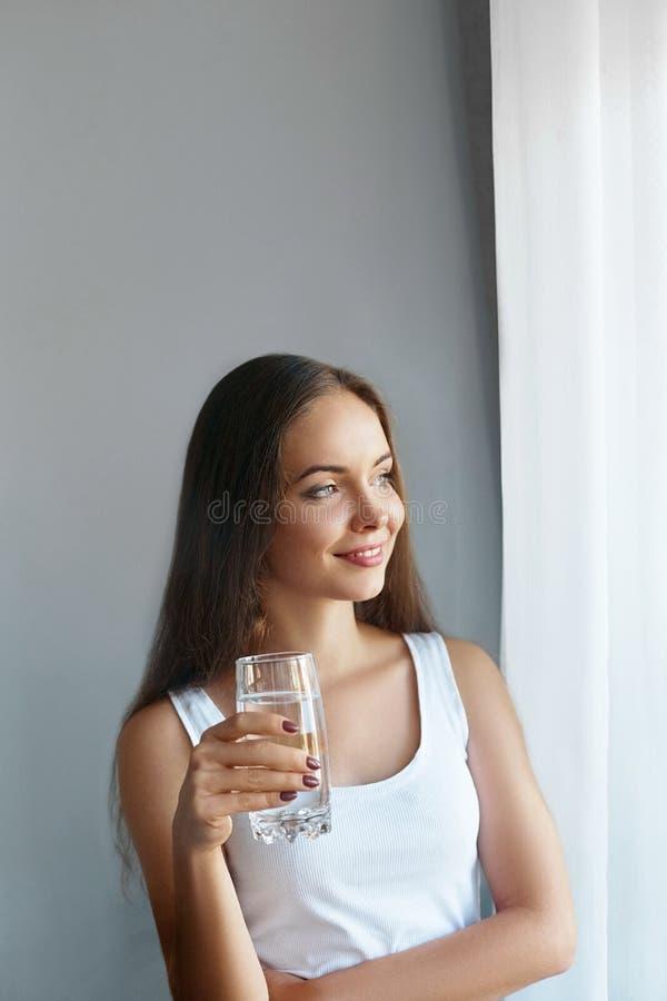 Sund livsstil Showexponeringsglas för ung kvinna av vatten dricker flickavatten Stående av den lyckliga le kvinnliga modellen royaltyfri fotografi