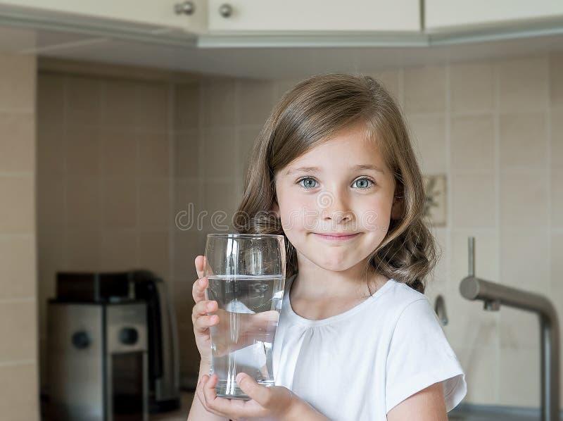 Sund livsstil Stående av den lyckliga le unga flickan med exponeringsglas Barn som hemma dricker sötvatten i köket h?lsa royaltyfria bilder