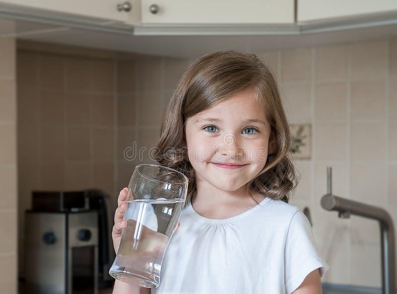Sund livsstil Stående av den lyckliga le unga flickan med exponeringsglas Barn som hemma dricker sötvatten i köket royaltyfri foto
