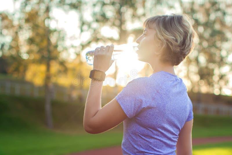 Sund livsstil Stående av den unga kvinnan med flaskan av vatten arkivfoton