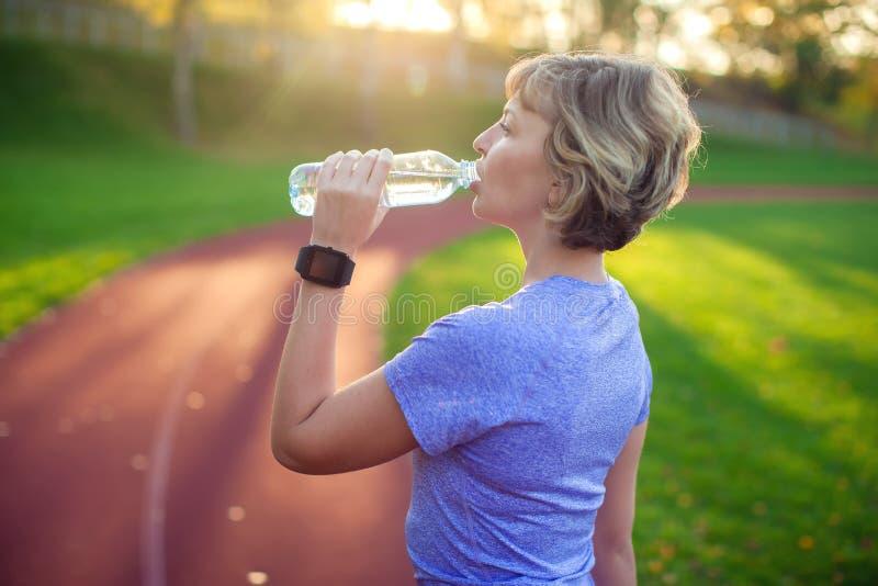 Sund livsstil Stående av den unga kvinnan med flaskan av vatten arkivbild