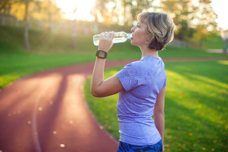 Sund livsstil Stående av den unga kvinnan med flaskan av vatten royaltyfria bilder