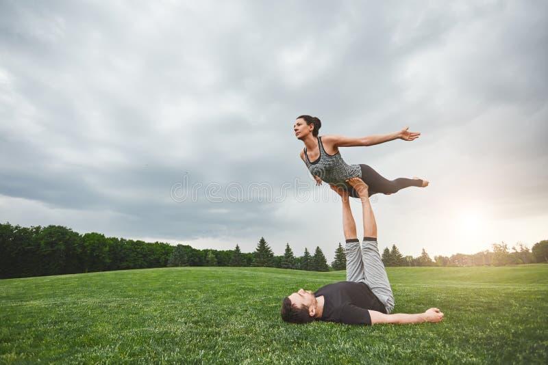 Sund livsstil Stark man som ligger på gräs och balanserar kvinnan på hans fot Praktiserande acroyoga för unga par in royaltyfria foton
