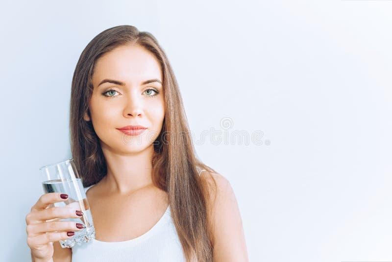 Sund livsstil Ung kvinna som dricker från ett exponeringsglas av sötvatten Sjukv?rd drinkar Stående av den lyckliga le kvinnliga  arkivbilder