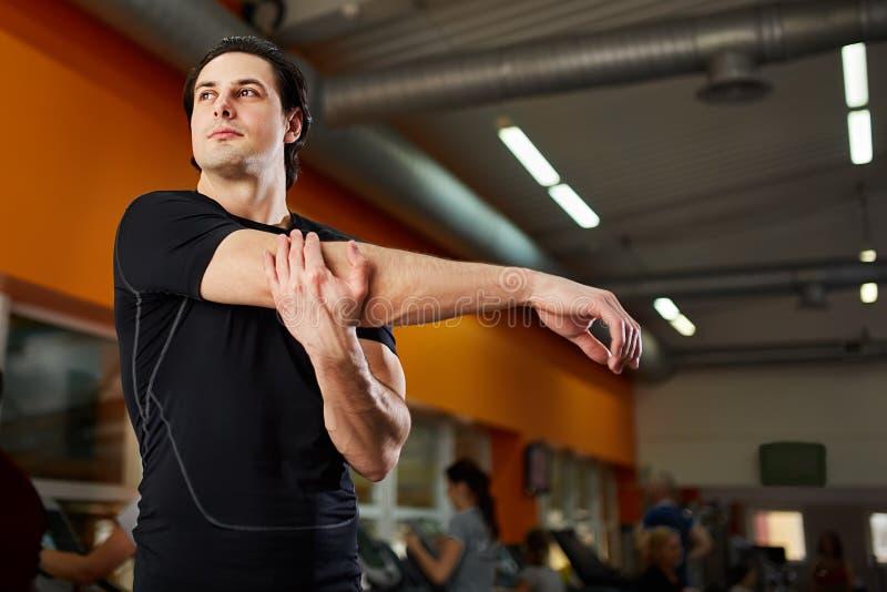 Sund man för ung idrottsman nen i den svarta sportwearen som sträcker skuldran för idrottshallgenomkörare royaltyfria foton
