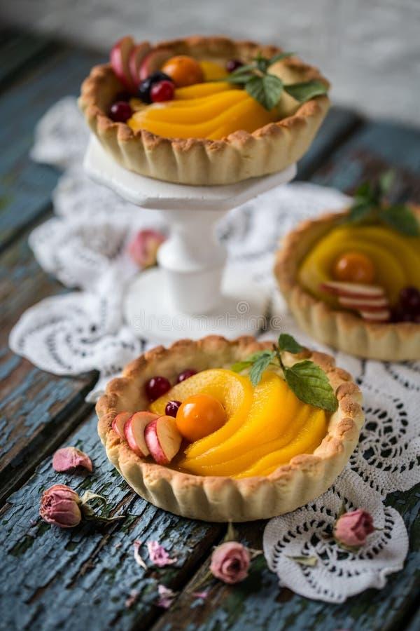 Sund mat är nya frukter och bär, persikor, äpplen, tranbär, uddekrusbär i en korg från deg royaltyfria bilder