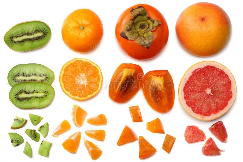 sund mat blanda den skivade persimonet, apelsinen, mandarinen, kiwi och grapefrukten med det gröna bladet som isoleras på vit bak arkivfoto