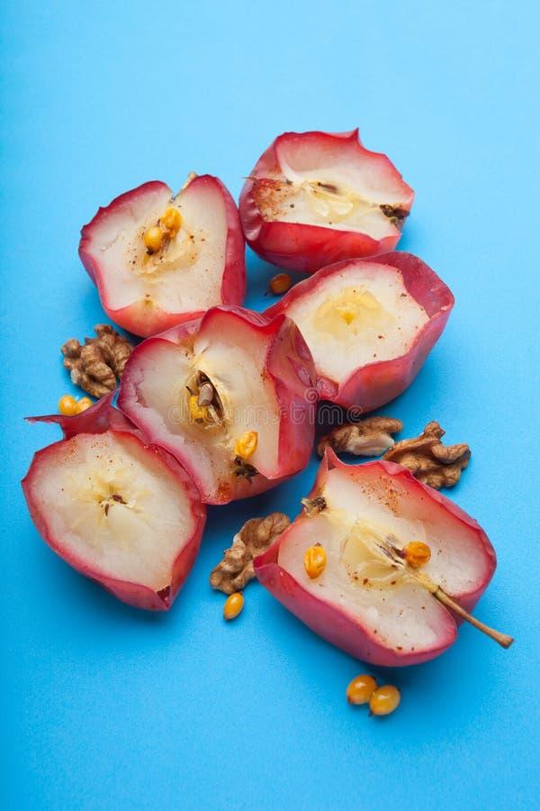 Sund mat för viktförlust från röda bakade äpplen med muttrar och vinäger på en blå bakgrund, vertikalt arkivfoton